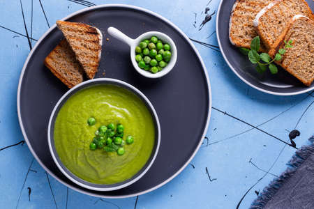 Fresh homemade peas cream soup with mint and toasted bread. 免版税图像
