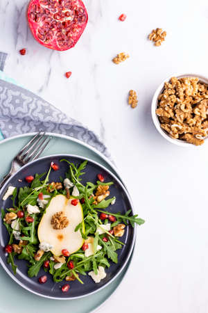 Fresh and healthy salad with arugula, gorgonzola cheese, pomegranate and pears.