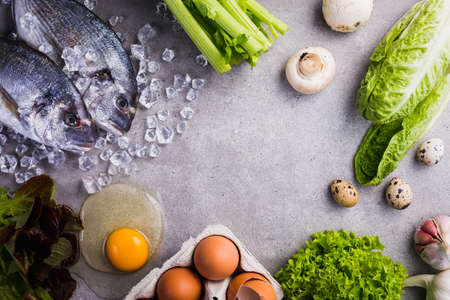 Frame of raw cooking ingredients for tasty and healthy food. Fresh dorado fish on ice, vegetables, eggs on gray concrete background top view.