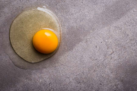Yellow yolk on concrete gray background.
