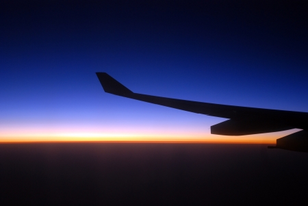 view from the airplane window at sunrise, with airplane wing