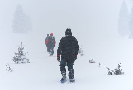 men goes through snow blizzard on snowshoes