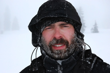 frozen man portrait in a blizzard, in a landscape covered with snow Stock Photo