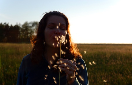 summer evening mood, girl blowing on a dandelion fluff photo