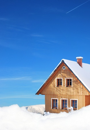 wooden cottage in winter in the mountains, under blue sky photo