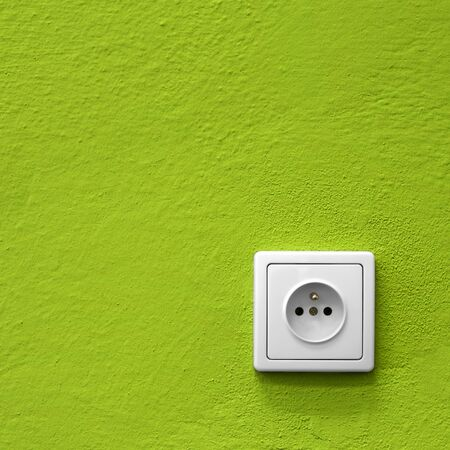 simple white electric socket on green wall photo