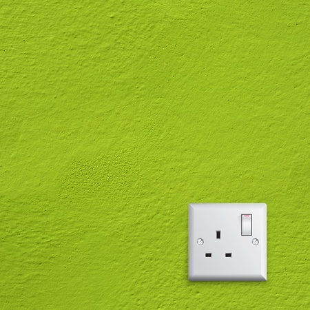 simple white electric great britain socket on green wall photo