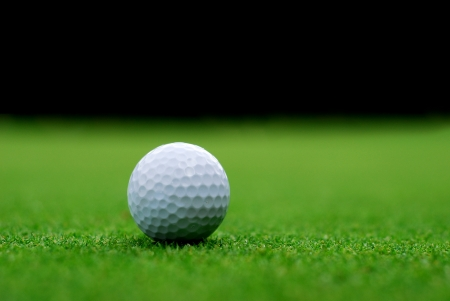 Golf ball on the green, blurred background Stock Photo