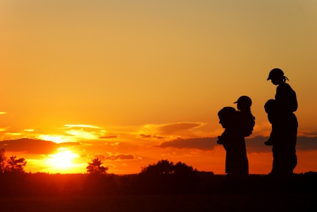 children on the shoulders of parents go summer evening, silhouettes on sunset Stock Photo