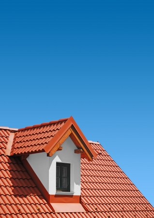 roofing: roof with red tiles with blue sky, new roof Editorial