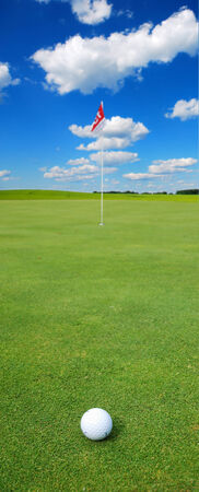 Golf ball in front of a flag on the green photo