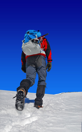 crampons: trekker with a backpack on snow, rising to the top of the mountain