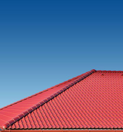 roof with red tiles on a background of blue sky, new roof Stock Photo