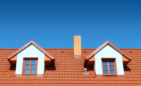 roof with red tiles on a background of blue sky, new roof Imagens