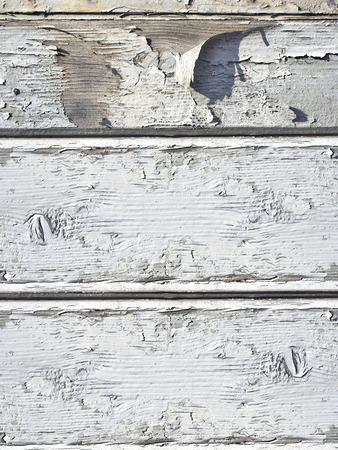 flaking white paint on wooden background
