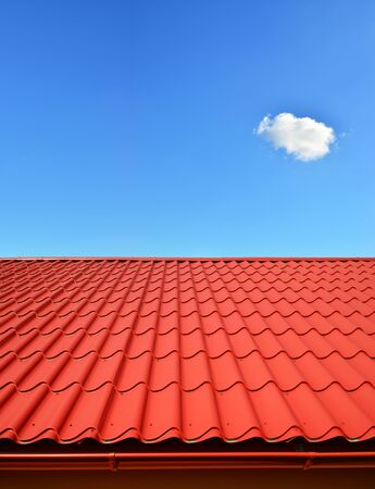 red metal background: new roof with orange red sheet metal and background of blue sky