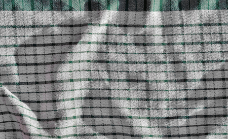 Background of slightly crumpled tablecloth with green and white cubes