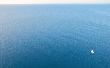 A sailboat on a blue ocean, covered only by water