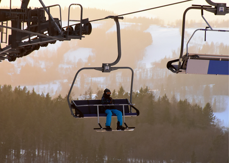 Skiing and snowboarding on the snowy mountains and riding on the chairlift Reklamní fotografie - 109586257