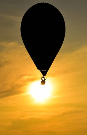 On the background of the sunset, hot air balloons fly and create silhouettes Imagens