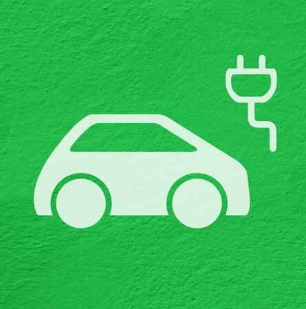 White pictogram, symbol of charging electric cars on green concrete