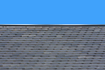 Roof made of black slate on a background of blue sky, new roof Stock Photo