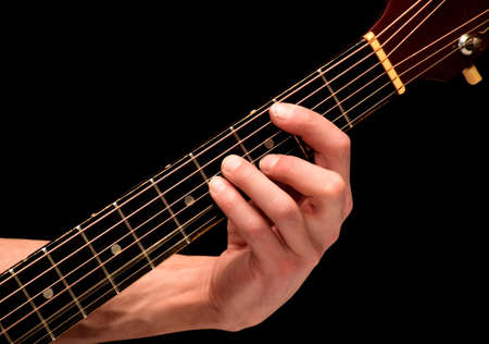 On a black background the playing guitarist chords on strings