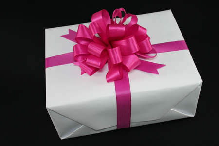 Big white present with ribbon on black background as sample for my gift objects