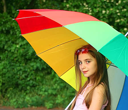 young girl in nature with big colored umbrella  Stock Photo