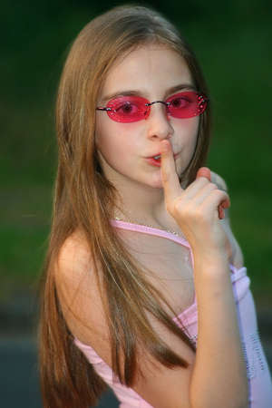 young girl making the silence sign, keep the secret Stock Photo