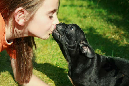 Girl kissing dog on summer day.
