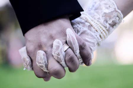 marido y mujer: Novio de la novia la mano fondo verde holdingon