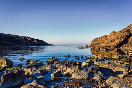 Rocks next to pebble beach on Black Sea under blue skies in Rumeli Feneri area, Black Sea, Sariyer, Istanbul, Turkey