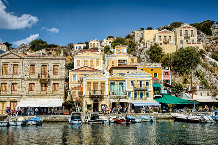 City center of the Greek island of Symi with pastel colored houses under clear blue skies, Agean sea Editorial