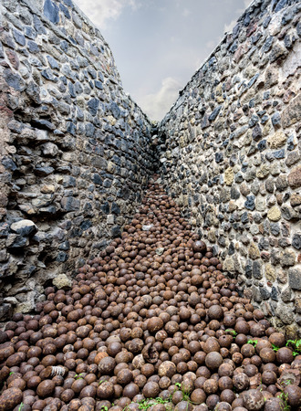 A pile of medieval rusted iron projectiles forming a superb perspective in a castle corner Banco de Imagens