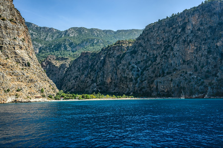 Butterfly Valley situated at the foothill of a two thousand meter high mountain with steep walls and a pebble beach Stock Photo