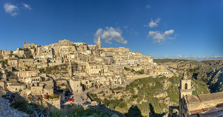A city on a rocky outcrop and a complex of cave dwellings carved into the mountainside Stock Photo