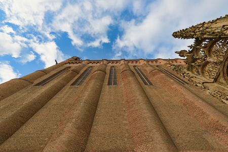 Closeup view from ground up of a medieval cathedral under blue skies with fluffy white clouds