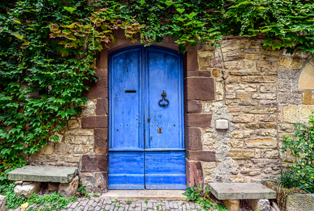 A blue and worn door with green ivy above on the stone walls of a small town in French countryside Archivio Fotografico