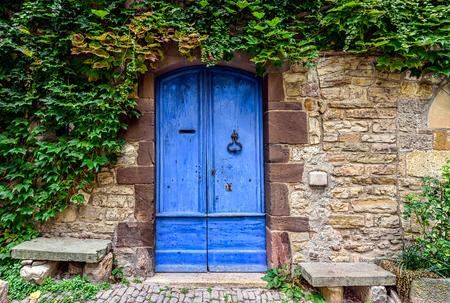 Una puerta azul y gastada con hiedra verde arriba en las paredes de piedra de una pequeña ciudad en el campo francés