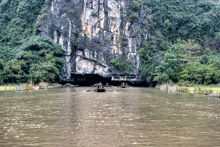 Boats rowing into a cave on a river in Vietnam