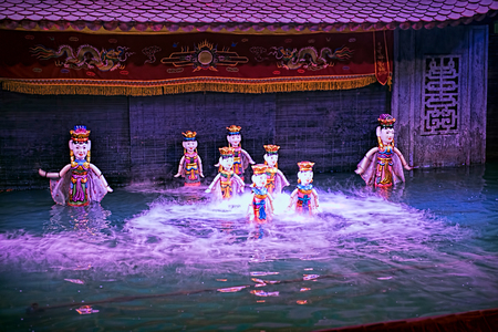 Water puppet show in Vietnam under purple lights Фото со стока