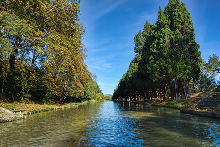Water canal in southern French town under clear blue skies