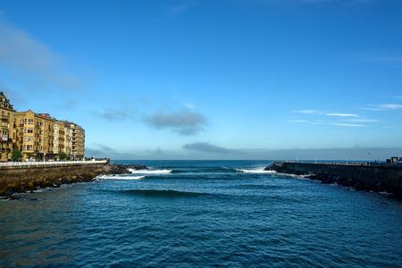 River Urumea mouth opening to Atlantic ocean in San Sebastian Spain under blue skies