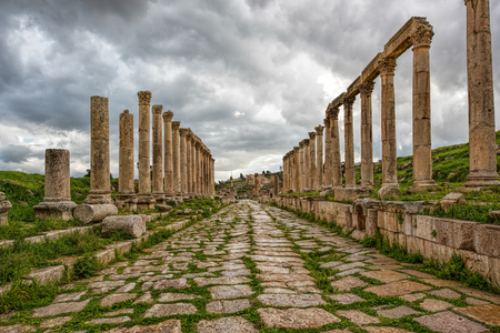 A  collonade street in the ancient city of Gerasa after a storm with dark grey clouds