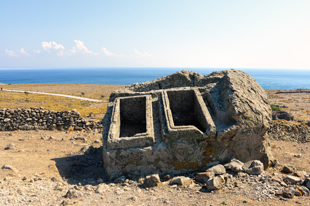 Long forgotten empty ancient tombs in an aegean island of Turkey under clear blue skies