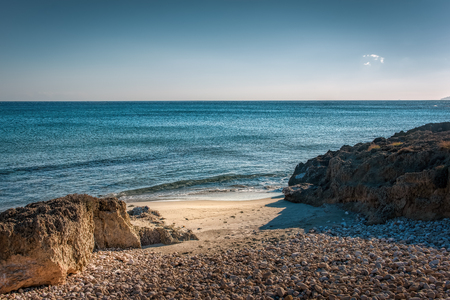 Crystal clear sea with rocks on a pebble beach foreground under blue skies