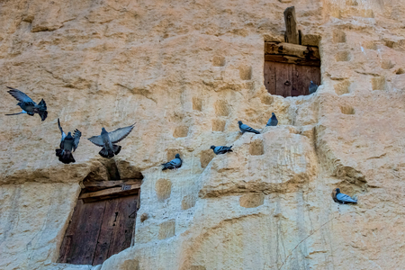 An ancient tradition, naturally cool stone carved warehouses along with many pigeon lofts for manure on a limestone cliff in Ermenek, Turkey Reklamní fotografie