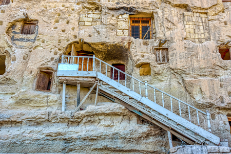 White iron stairs leading to one of the naturally cool, stone carved warehouses along with many pigeon lofts for manure on a limestone cliff in Ermenek, Turkey, an ancient tradition