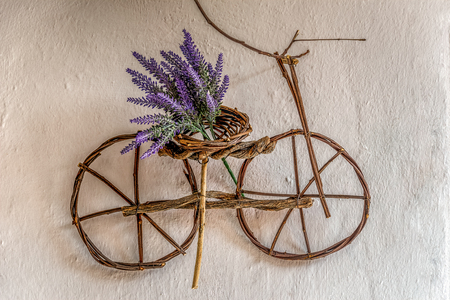 Purple wildflower on small bicycle ornament handmade using thin tree branches hanging on an old wall